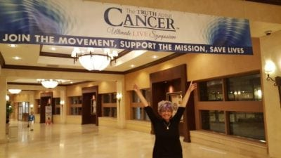 Woman in Front of Truth about cancer banner